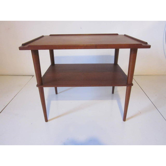 A dark teakwood two-tiered side table with raised edge designed top and sitting on console legs, branded mark to the...