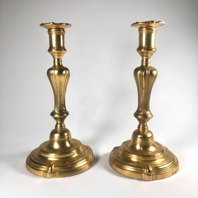 A pair of finely cast and hand-chased ormolu (fire-gilt copper alloy) candlesticks in the Rococo taste, likely having the...