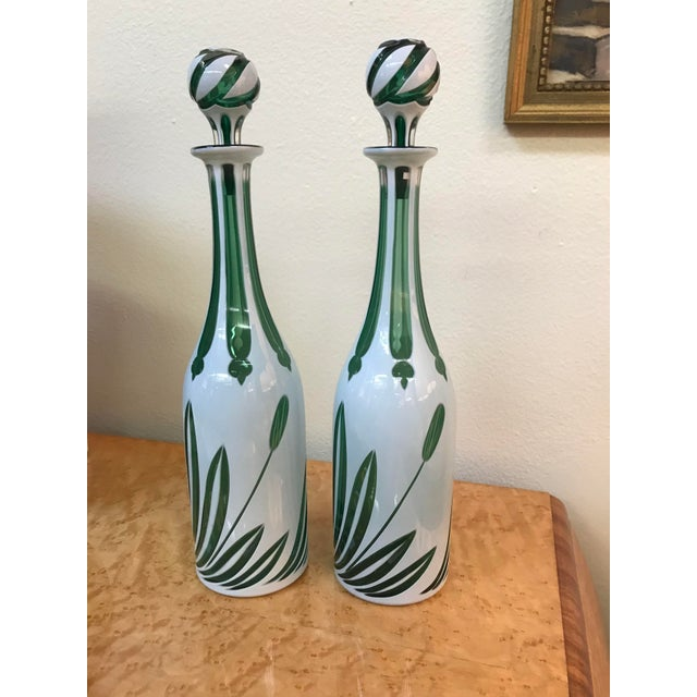 """A wonderful pair of tall green and white """"cased"""" glass bottles with stoppers (glass cased in enamel), from England, mid..."""