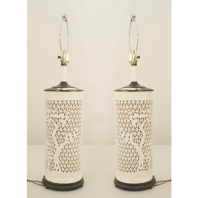 Pair of Asian Chinese style (1950s) white porcelain cylindrical shape table lamps with a filigree design of trees and...