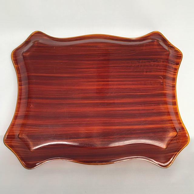 Vintage rectangular plastic serving tray with translucent wood grain finish and Chippendale style edge.
