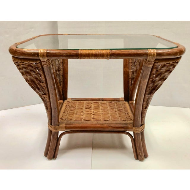 Unique Rattan Side Table. Mid-century classic curves. Perfect combination of solid rattan and delicate wicker. Glass top...