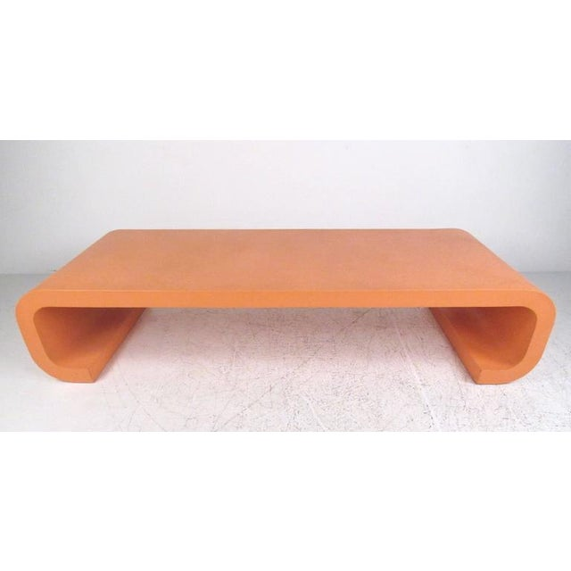 This large grass-cloth finish coffee table has a unique orange/pink paint job, with Karl Springer style scrolled legs. Its...