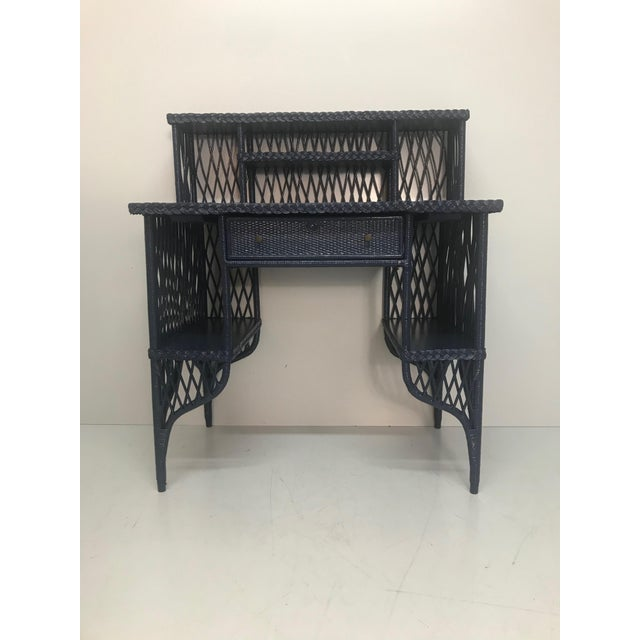 Navy rattan writing desk with topper. The desk contains a drawer, two side cubbies, and a shelving topper. Beautiful...