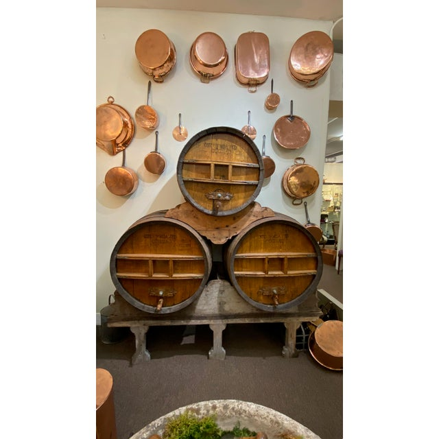 A set of three 19th century wood Ozcuf and David Cognac barrels with metal banding and original spouts for pouring all...