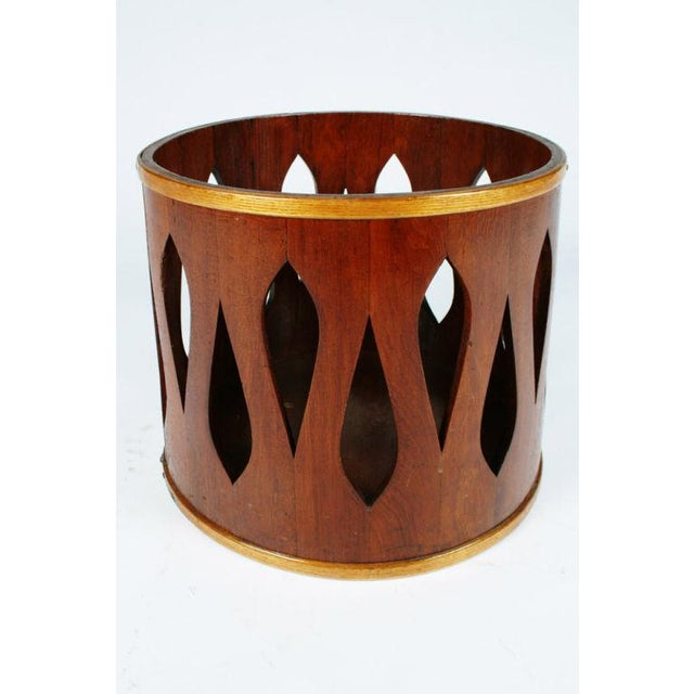A mod wastebasket in staved teak wood with an abstract teardrop shaped piercing to its side. By Jens Quistgaard for Dansk....