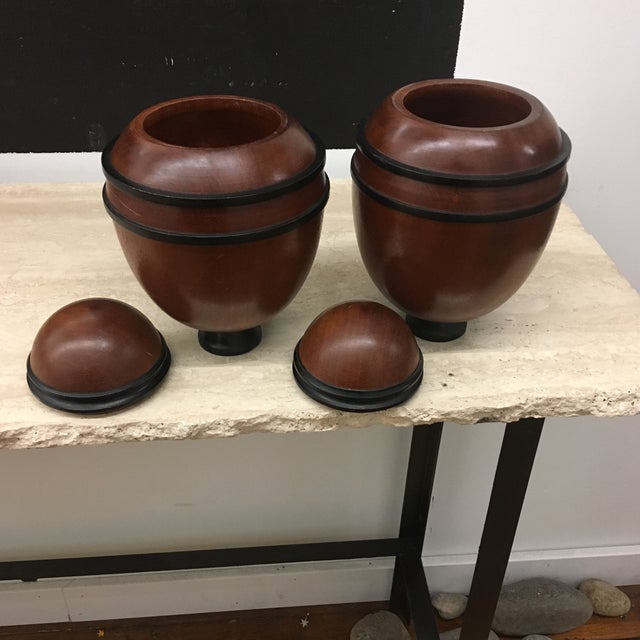 Two wooden hand turned urns , not identical But made for the same company. One Urn has a slit on either side. As this was...