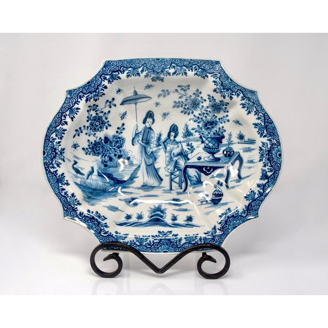 Delft platter marked on the underside of base with a blue on white design of two Chinese figures with pea hens and...