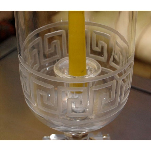 Striking Hurricane candle holders of etched glass with Greek Key motif. There is a glass candle stick in the center of...