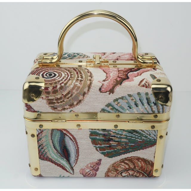 Fun and functional Lisette of New York train case style handbag with a gold tone metal frame and a seashell motif tapestry...