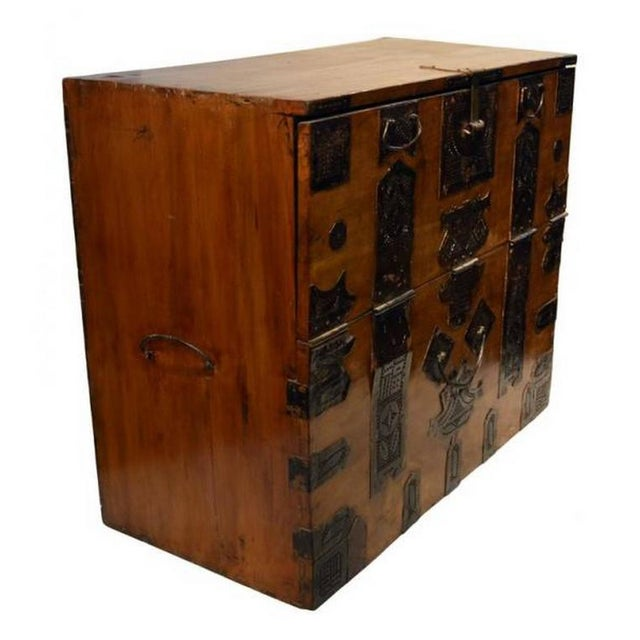 A Korean blanket chest featuring decoration of stylized ornate hardware.  This small chest is made - High-End Antique Korean Blanket Chest With Carved Ornate Hardware
