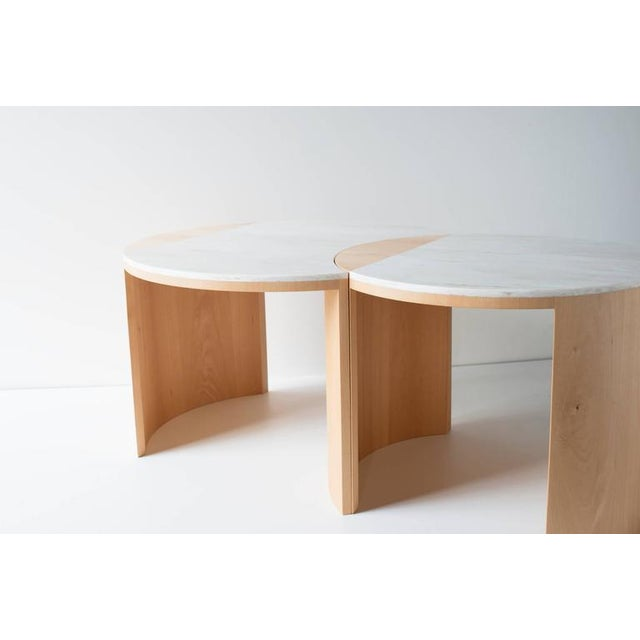 The gibbous coffee table is built in bent plywood, veneer, and Corian. The smaller table is nesting and rotatable,...