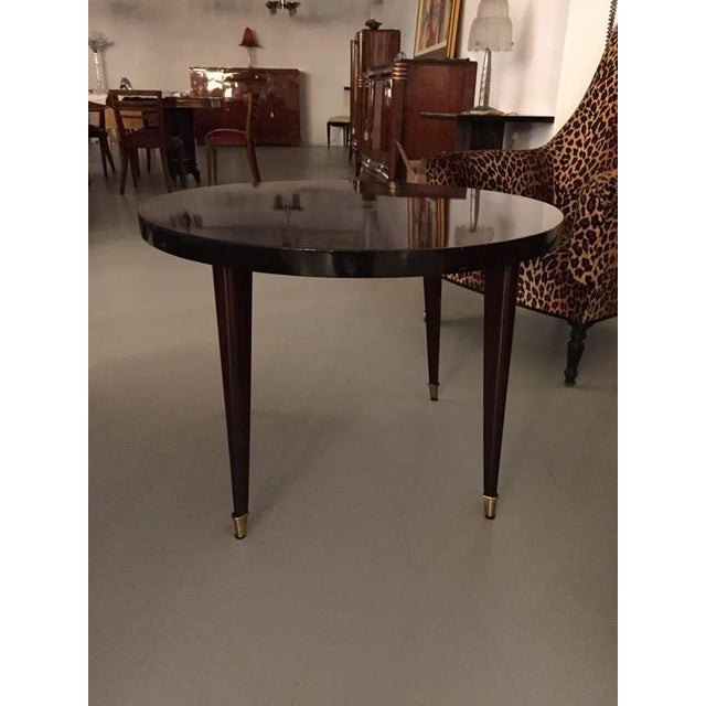 A round French Art Deco occasional table. Having tapered legs with bronze sabots.