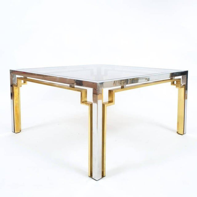 A beautiful coffee table attr. to Romeo Rega featuring a double chrome & brass frame encasing a floating slightly smoked...