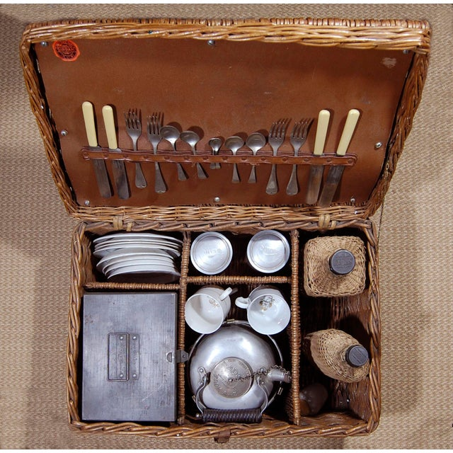 A Vintage English ' Sirram ' Wicker Picnic Basket, outfitted completely. 1 brass burner, 2 aluminum canisters (1 with 1/4...