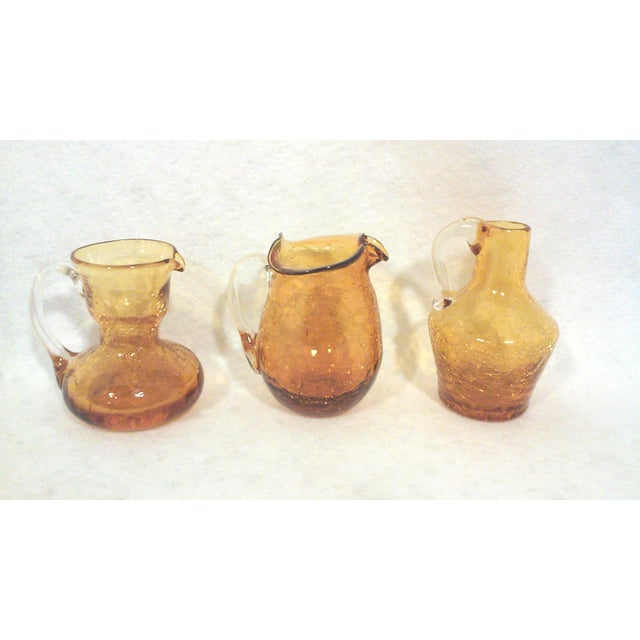 Blenko gold crackle vases set in three complimentary shapes. These mid-century American art glass vases are a great size...