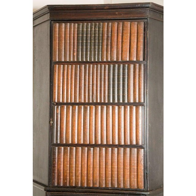 1840s English corner cupboard with faux front panel door. Handsome painted corner cupboard with a fabulous faux books...