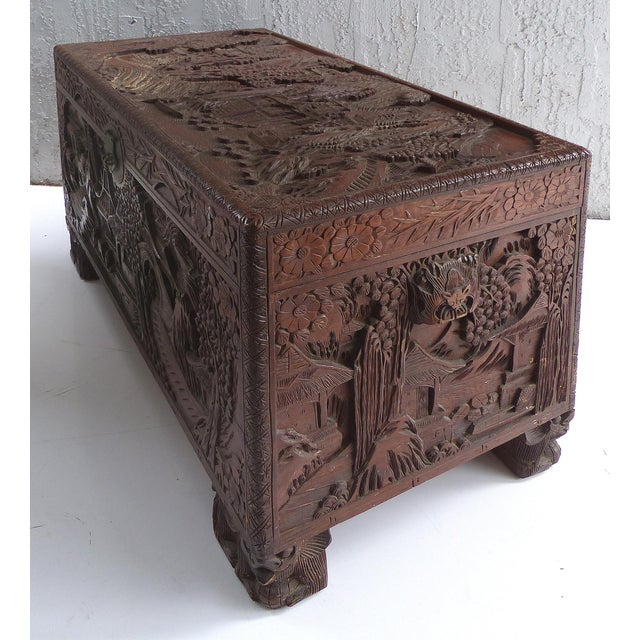 Offered for sale is a carved Chinese teak & cedar wood trunk with a brass latch. The chest is carved on all sides and the...