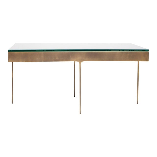 Bronze cocktail table with fitted clear glass top.Solid flat bar metal frame with on thin profile legs with interior...