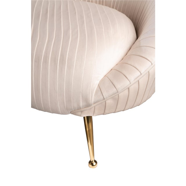 Airy yet edgy, our Beatrice Curved sofa is upholstered in off white velvet fabric and perched on polished brass stiletto...