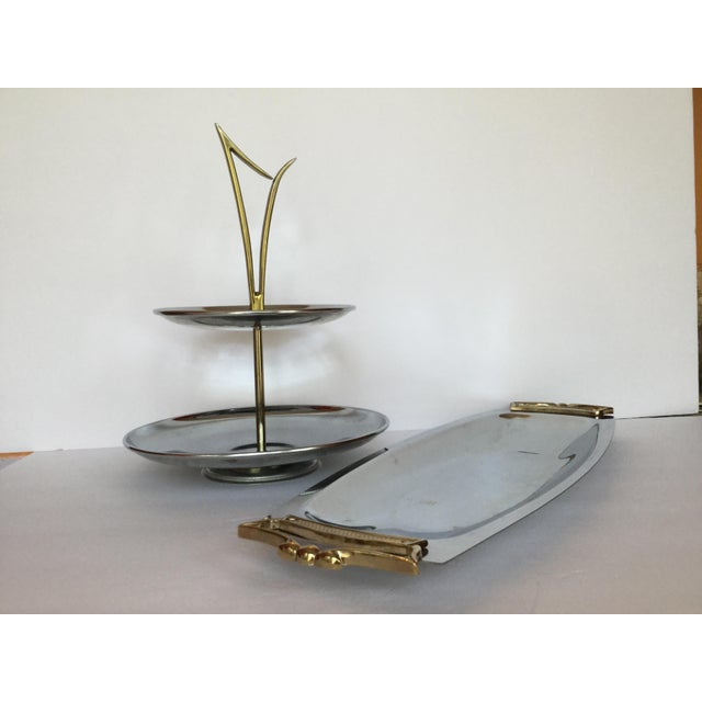 This pair of brass and metal serving pieces are delightfully mid-century. The tiered serving piece is made of two round...