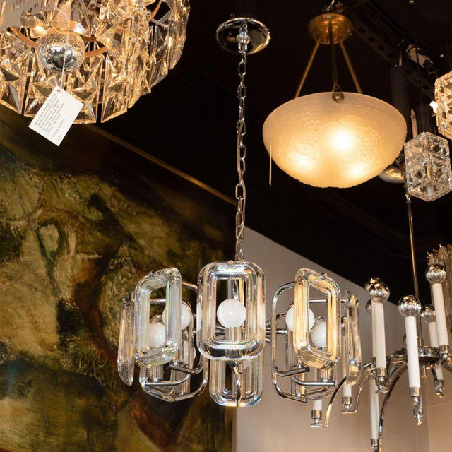 This stunning and graphic Mid-Century Modern chandelier was realized in the United States, circa 1970. It features a...