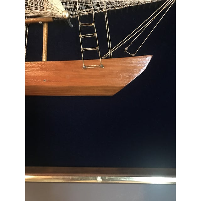 This is large sailing vessel made with a carved wooden hull and string for the sails, on a dark blue/navy velvet...