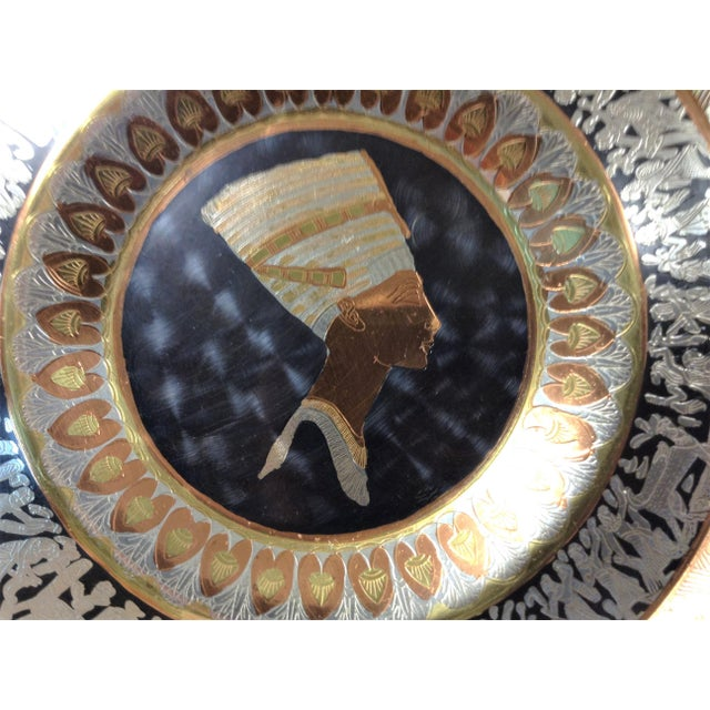 Egyptian Copper Plate depicting Nefertiti This plate measures approximately 9 1/4 inches across. It has a hook on the back...