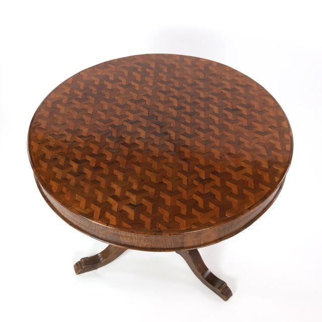 An Italian Walnut Round Pedestal Base Center Table with a concave hexagonal parquetry inlay pattern employing three...