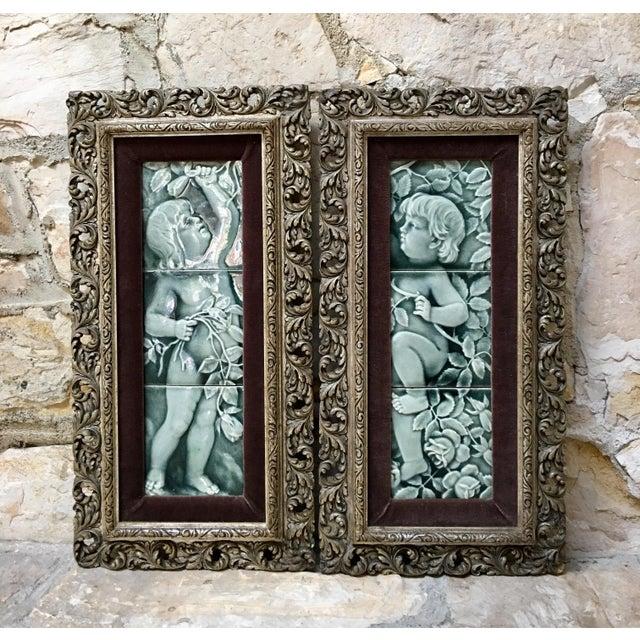 A pair of framed three piece figural tile sets in an ethereal blue gray glaze depicting cherubs amid rose vines. These...