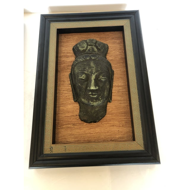 A superb pair of Hollywood Regency sculptural relief Buddha heads mounted on grasscloth backgrounds and framed stylishly...
