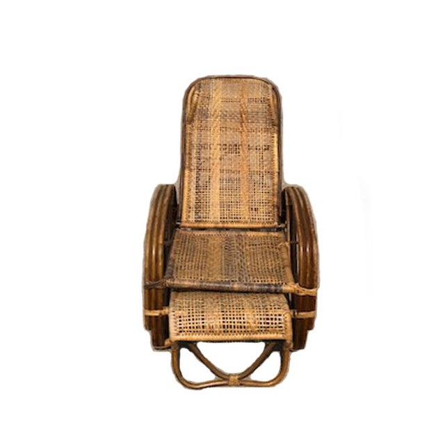 This is a vintage rattan bamboo reclining lounge chair with built in ottoman. A lightweight easily movable chair. Four...
