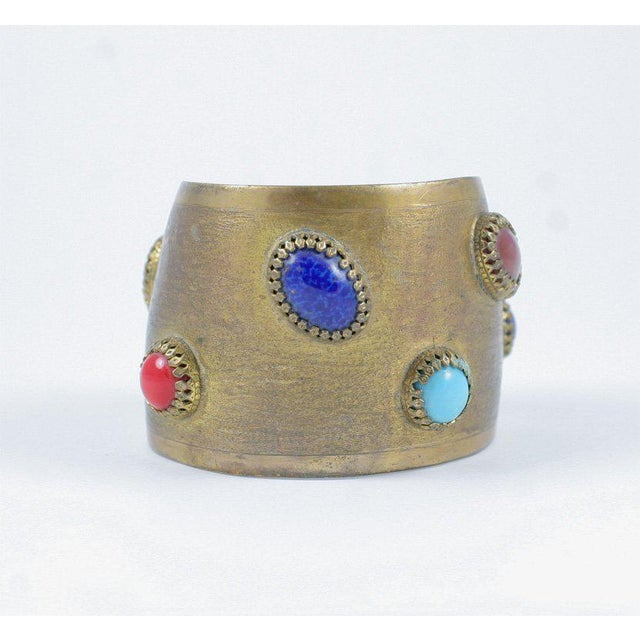 Antique brass finished cuff adorned with faux semi precious cabochon stones. Due to the unique nature of this product, all...