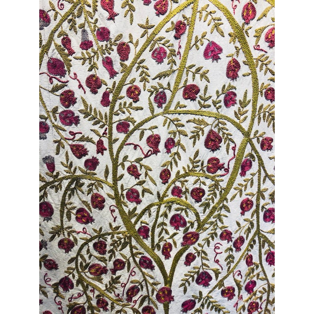 Hand-embroidered cotton suzani depicting pomegranates, flowers and vines. Stunning raspberry color set against creme with...