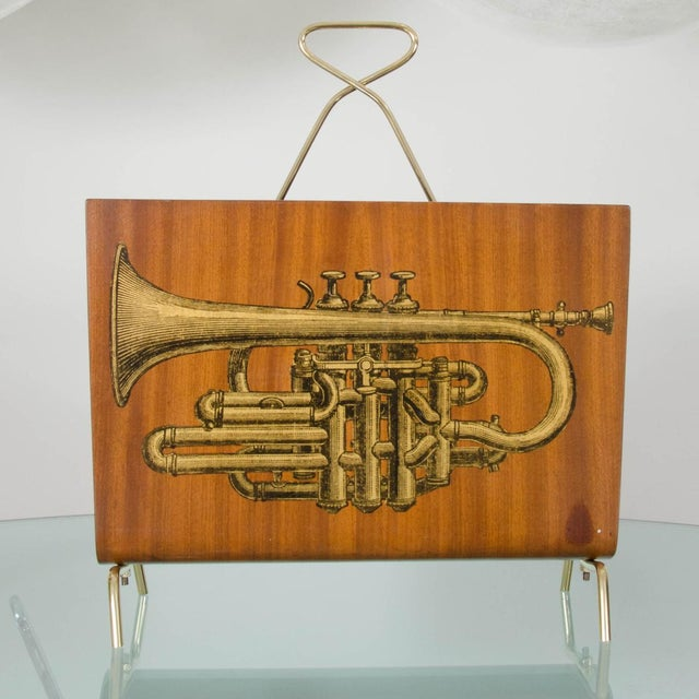 Blonde wood curved magazine rack with musical instrument motif and brass details.