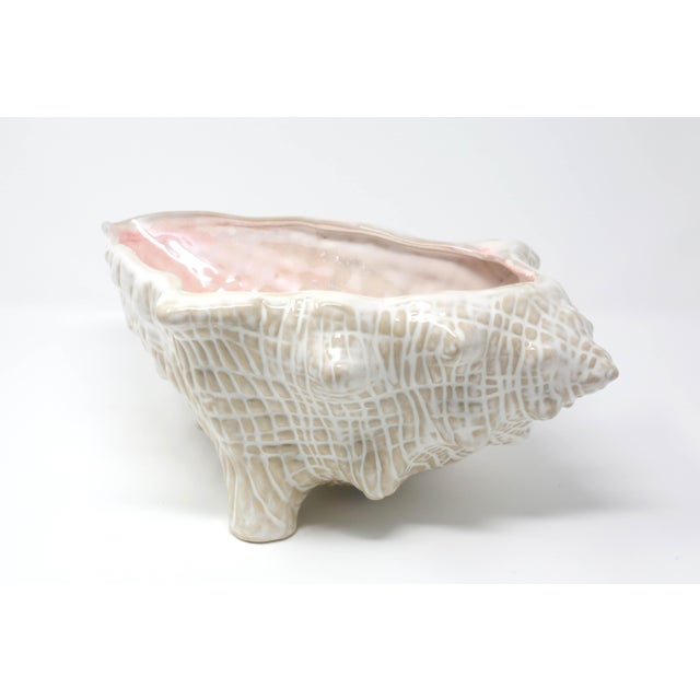 A large, ceramic bowl, in the form of an oversized conch shell. Beautiful detail in the design and glazing. Excellent...