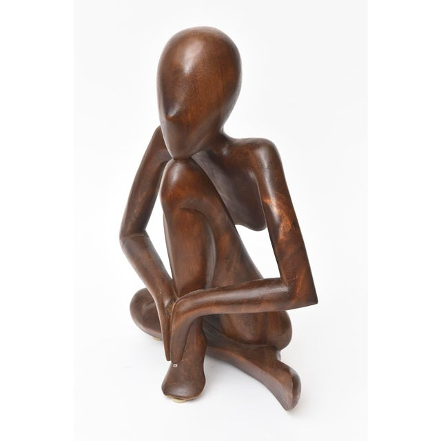 This mid century modern wood sculpture has elements of African influences. The wood may be walnut and is carved...