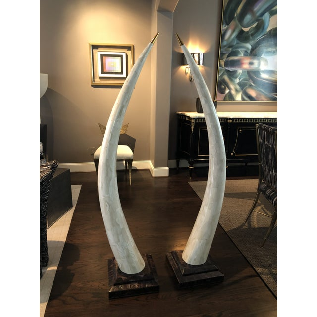 A pair of contemporary FAUX tusk sculptures makes a grand statement. These are made of inlaid clam stone with a brass tip....