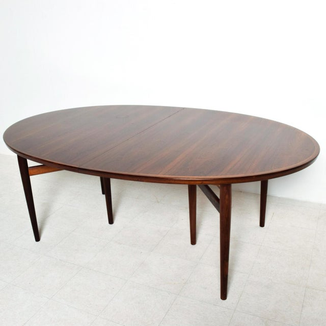 We are pleased to offer for your consideration a beautiful rosewood dining table with an oval shape. Designed by Arne...