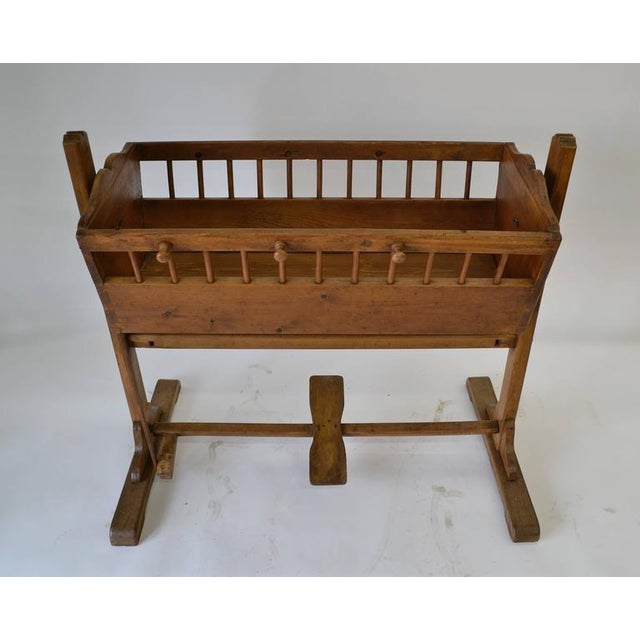 An outstanding pine cradle on a trestle base of oak and beechwood, in almost entirely original condition. Operating the...