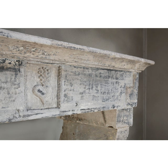 Beautiful antique French limestone mantel fireplace from the 19th century. This mantelpiece is in the style of...