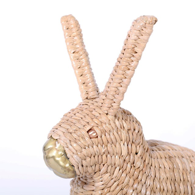 Adorable midcentury bunny or rabbit crafted in wicker, wrapped over a metal frame with a brass nose and copper eyes....