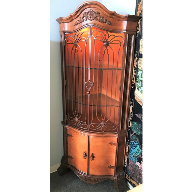 Very unique corner cabinet! Made of simulated wood with open scroll work iron doors with a key design. Two adjustable...