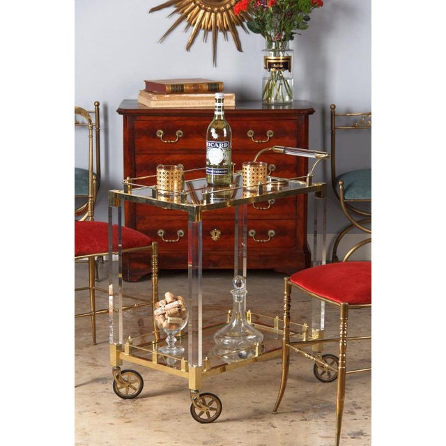 A wonderful bar cart from Spain, circa 1970s. The cart features brass rails and frames, lucite legs and a brass and lucite...