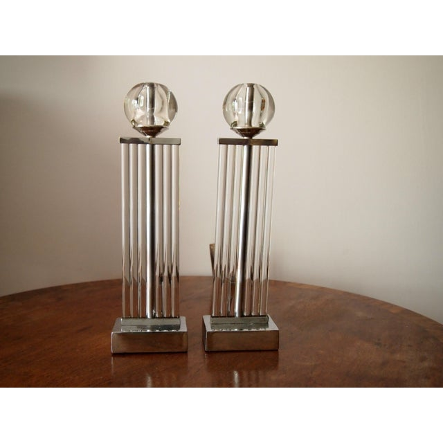 Spectacular pair of Art Deco chrome and glass andirons. Each with solid glass columns sitting atop a solid chrome base...
