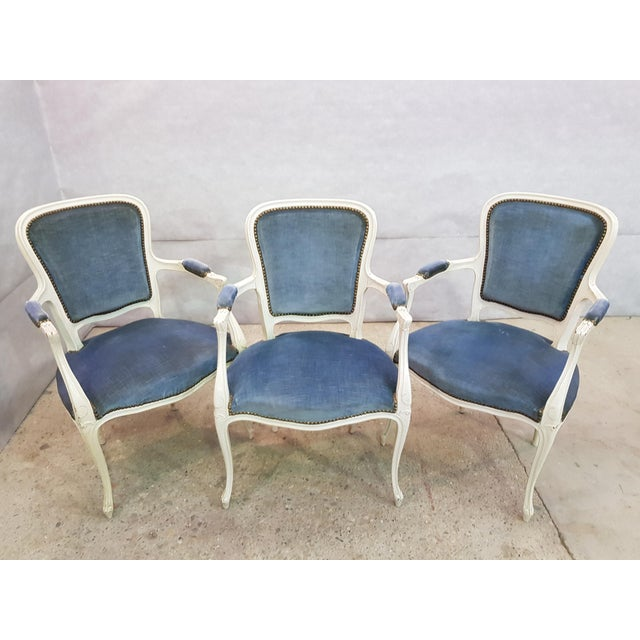 Set of Three Large Vintage Louis XV French Hand Painted White Armchairs with Blue Velvet Upholstery. The chairs are...