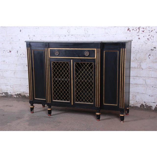 A gorgeous neoclassical style sideboard credenza or bar cabinet by Baker Furniture. The cabinet features a black lacquered...