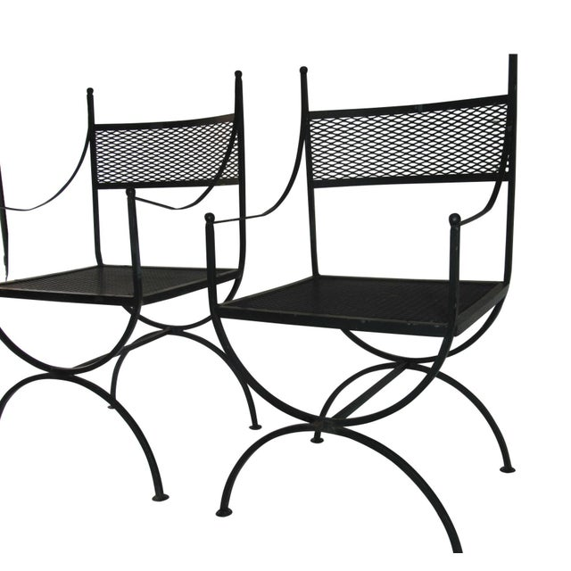 "Pair of John Salterini ""curule"" chairs comprised of wrought iron, with iron mesh seats and backs, and iron ball finials...."