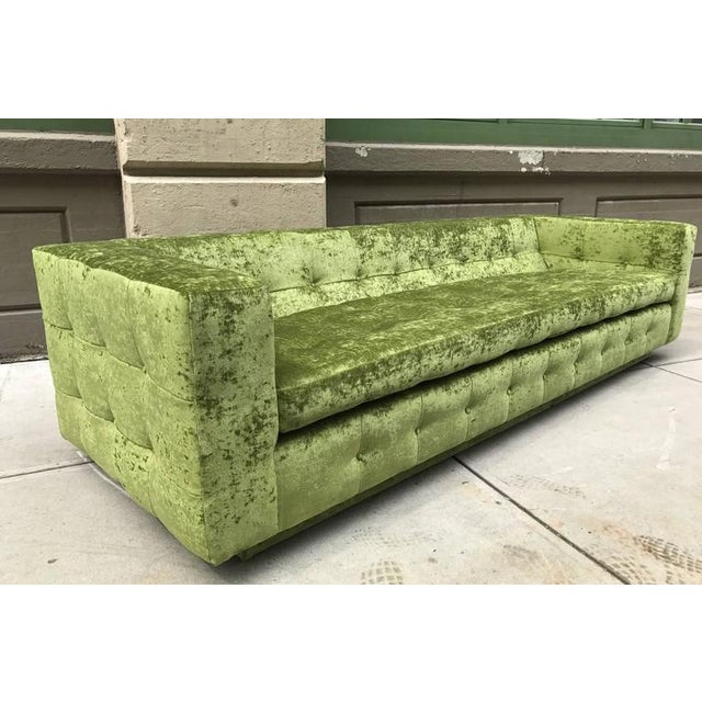 Custom tufted sofa newly upholstered in green velvet on plinth base. Has loose seat and side cushions. The sofa shown is...
