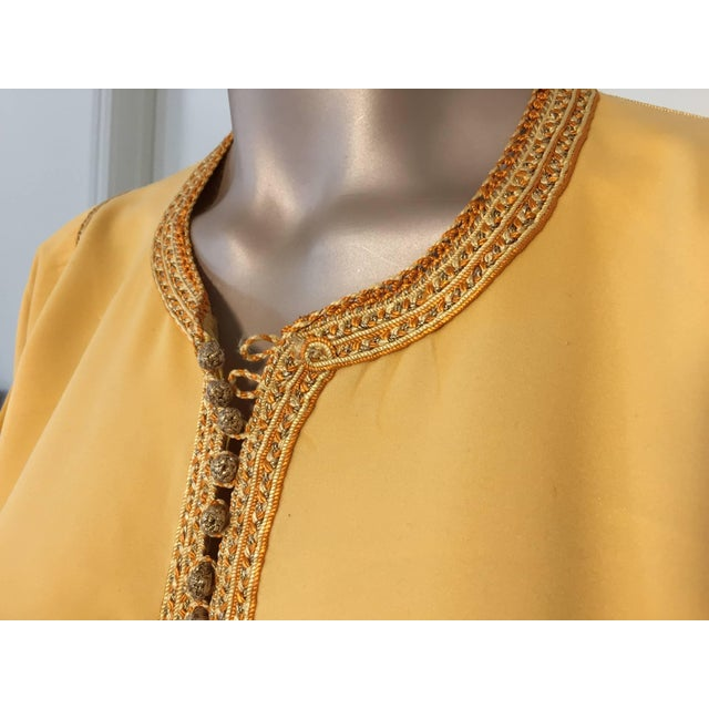 Elegant Moroccan caftan yellow gold color embroidered with gold trim, circa 1960s. This long maxi dress kaftan is...